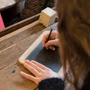 Eleverne skriver med pæn og blæk og med griffel på skiffertavler i den historiske skolestue foto Johnni Pape